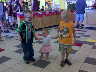 Two little boys each holding the hand of a toddler between them.