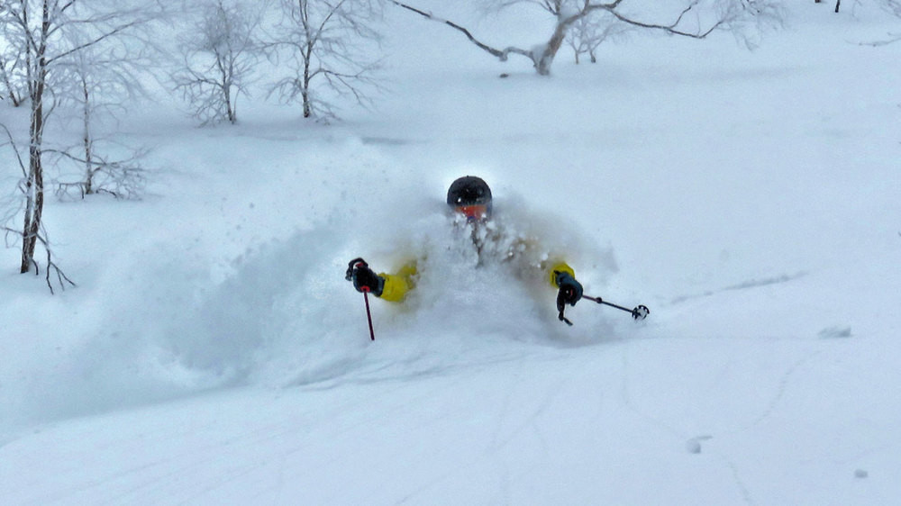 A skier waist deep in soft, dry backcountry pow in Furano.