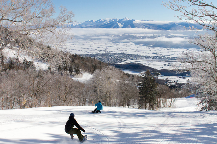 Two snowboarders taking advantage of perfect conditions on spacious Furano ski slopes.