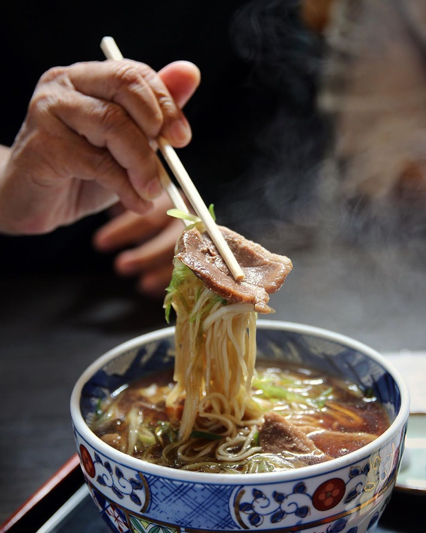 A hand with chopsticks lifting up some miso ramen out of a bowl