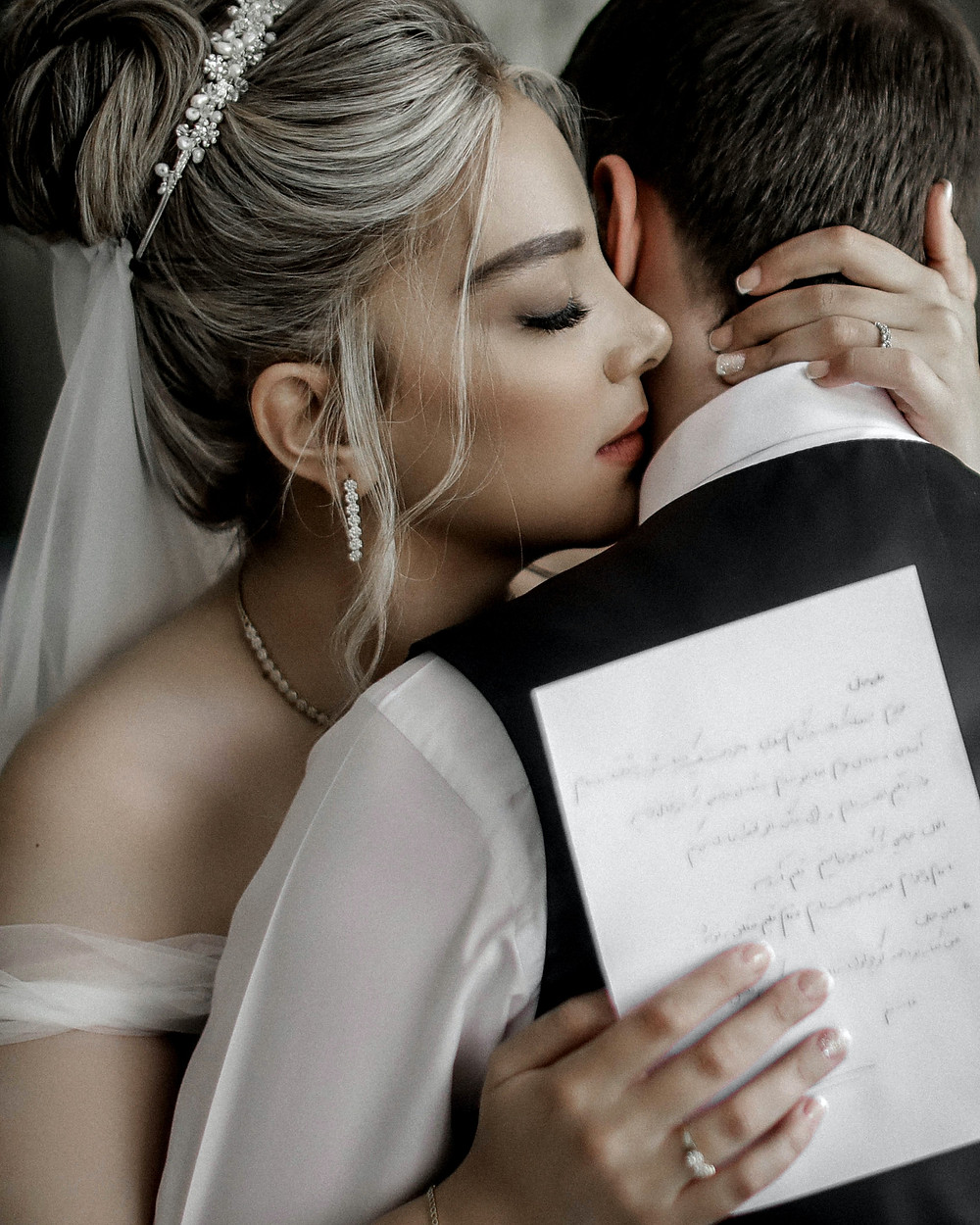 A white couple hugging. She is blonde and has a veil in her hair, and is wearing a wedding dress. She is holding a paper with vows written on it. He has his back to the camera, and is wearing a white collared shirt and a black vest.