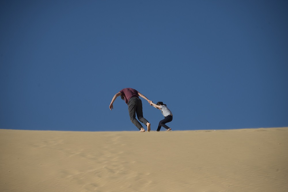 Father and daughter playing on dune