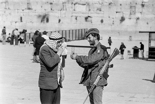 Jerusalem, An Israeli soldier lights a cigarette for an Arab  By Jacob Elbaz