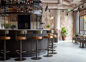 Picture of a bar with tall bar stools and plants inside a restaurant
