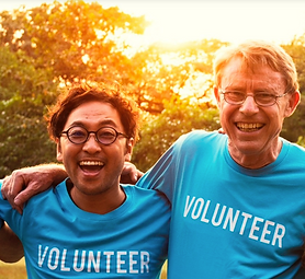 Picture of two men smiling wearing blue volunteer t-shirts