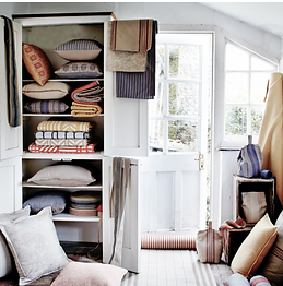 An open cupboard filled with coloured blankets and cushions next to a window