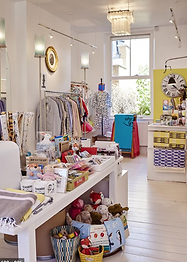 Image of the inside of a white store filled with children's toys and clothing