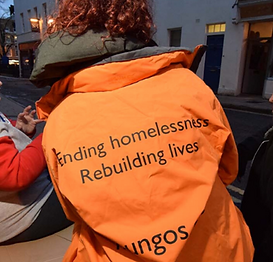 Image of a woman in an orange St Mungo's jacket facing backwards