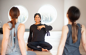 Image of woman teaching yoga to two students