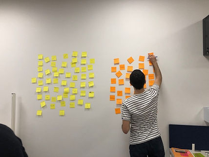 Man sticking a post-it on a wall during a workshop