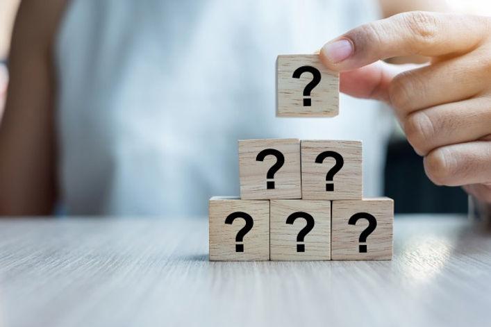 businesswoman putting up question mark cubes