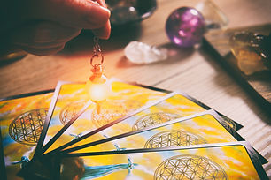 Tarot cards dowsing tool in hand and cry