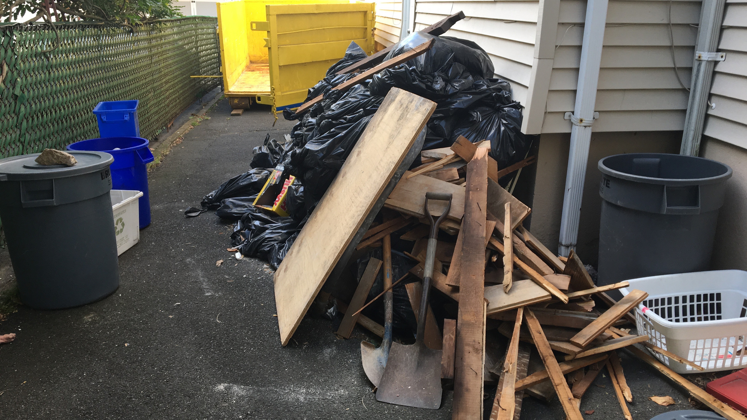 The dumpster is close to the pile.