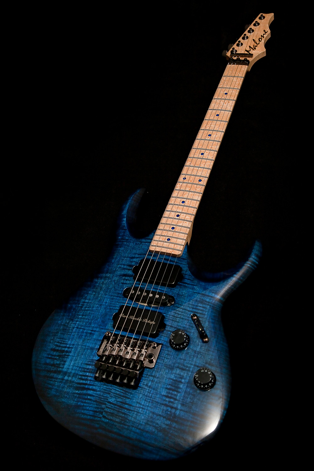 The image is a full shot of an electric guitar. the guiter has a blue and black flame-like striped body. The neck is made from birds eye maple. The hardware is black. The guitar looks awesome