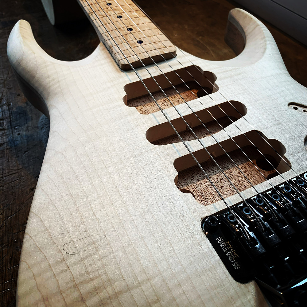 The image is a close up of the bare wooden body of an electric guitar and tremolo system. The guitar is incomplete and has no pickups installed, but has strings