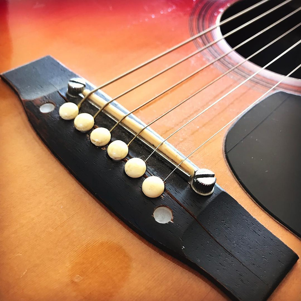 a badly cracked guitar bridge which was repaired at Malone Guitars in Billericay Essex