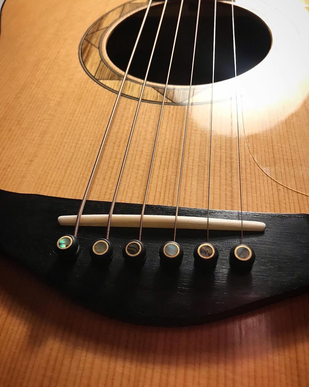 close up of the ebony bridge bone saddle and black limba rosette and soundhole of a Malone Guitars auditorium acoustic handmade in Essex UK