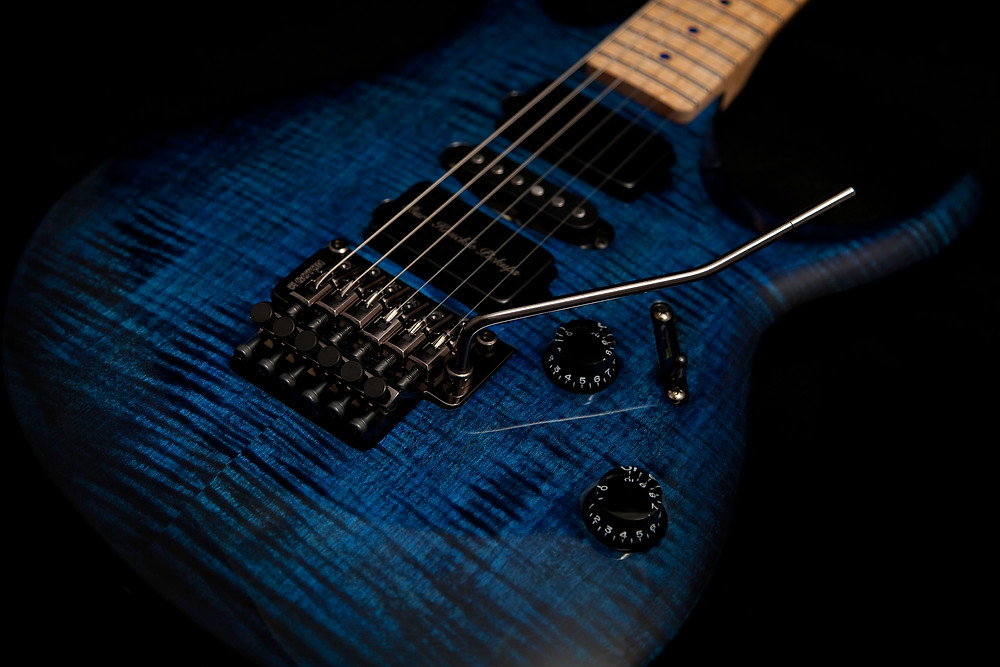 The image is a close up of the body of a blue and black rock guitar, which has a dyed finish showing the grain in the wood. The guitar has a two point tremolo system and three pickups