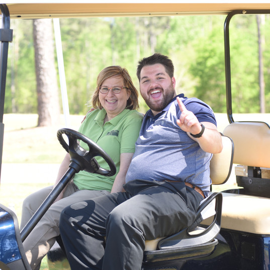 Taylor and a volunteer at a charity golf tournament
