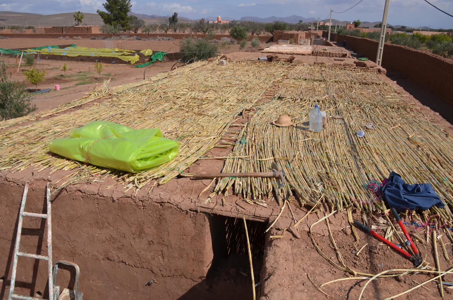 Bâche plastique contre la pluie recouverte de terre, puis de roseaux pour l'isolation avec tuyau d'évacuation des eaux de pluie et on finit par une couche de terre...