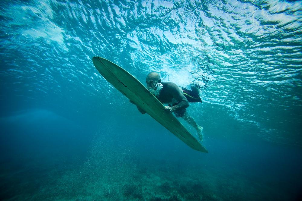 Tom Pohaku Stone on his surfboard