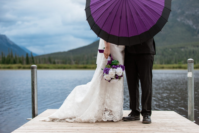 Bride and groom standing behind their purple umbrella in front of the water at Banff National Park