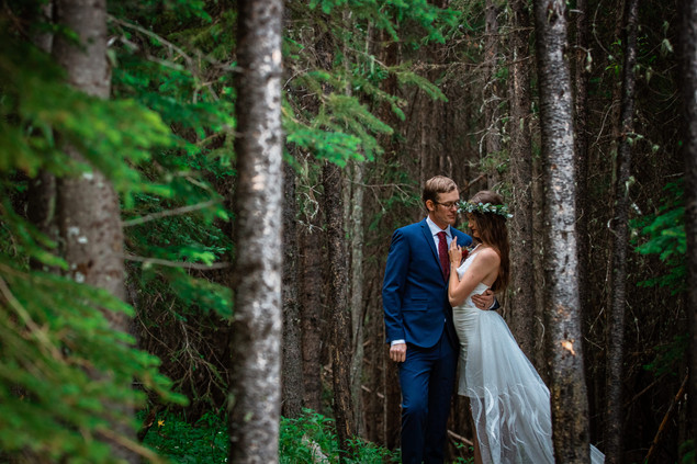 Bride and groom embracing in the trees in Kananaskis.