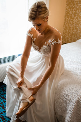 the bride sitting on a bed in her wedding dress putting her shoes on.