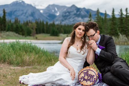 Bride and groom sitting on a blanket having a picnic at Cascade ponds, groom is kissing brides hand.