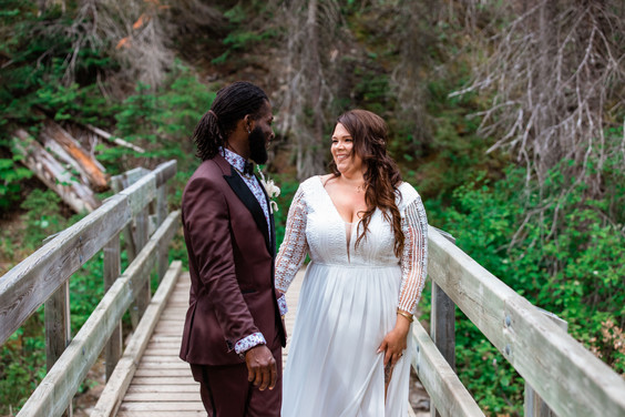 Bride and groom standing on a wooden bridge looking at one another.