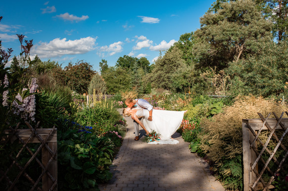 groom dipping bride and kissing her on a pretty path,