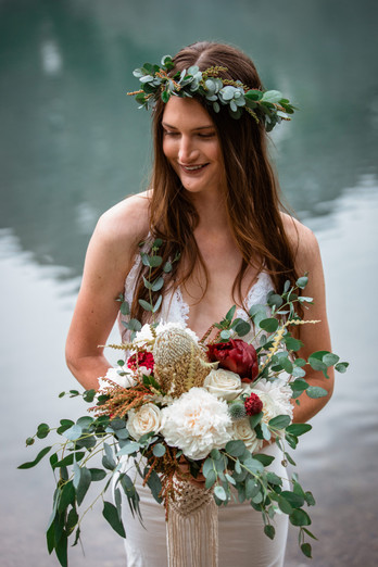 Bride in front of the water holding her bouquet.