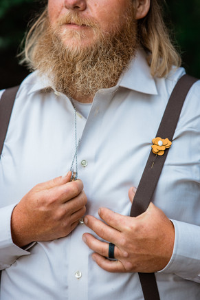 Upclose picture of the groom holding his ring on a necklace. He has a pin on his suspender of a yellow flower.