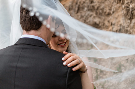 Bride holding the grooms shoulder and they are covered by her viel
