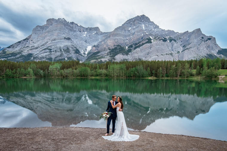 Bride and groom standing in front on the water in Kananaskis. Mountain in the background.