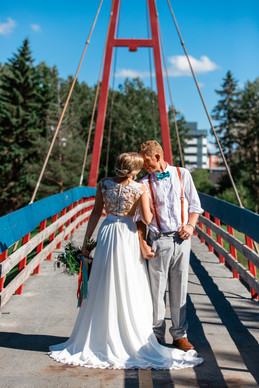 bride and groom standing on a suspension bridge embracing.