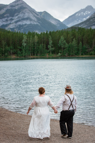Bride and groom standing in front of the water that is lined with trees.