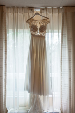 wedding dress hanging in the window so you may see the full length of it