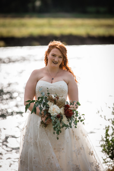 Bride standing in front of the water showing the detail in the top of her dress and her bridal bouquet.