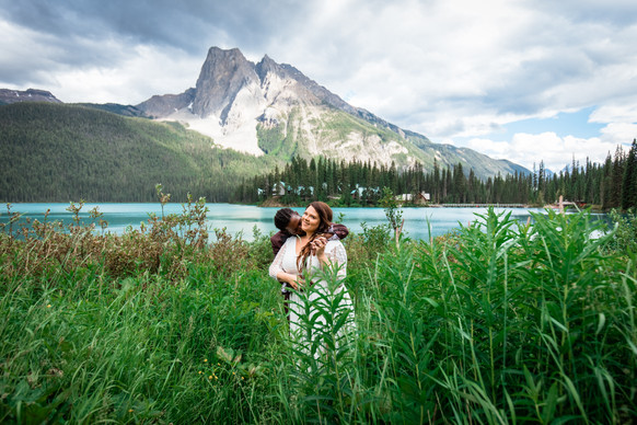 Groom kissing his bride on her neck from behind standing in a field of grass and flowers with Emerald Lake behind them.
