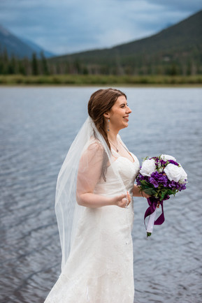 Bride standing in front of the water holding the edge of her veil and her bouquet