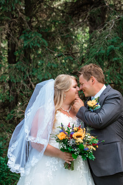 Groom gently touching his brides chin about to kiss her. Standing in the garden with big trees behind them.