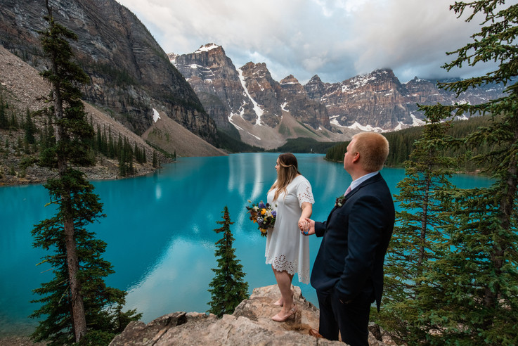 Bride and groom standing on big rocks holding hands looking out onto Moraine Lake.