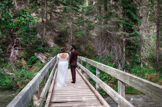 Bride and groom walking on a wooden bridge over Emerald Lake.
