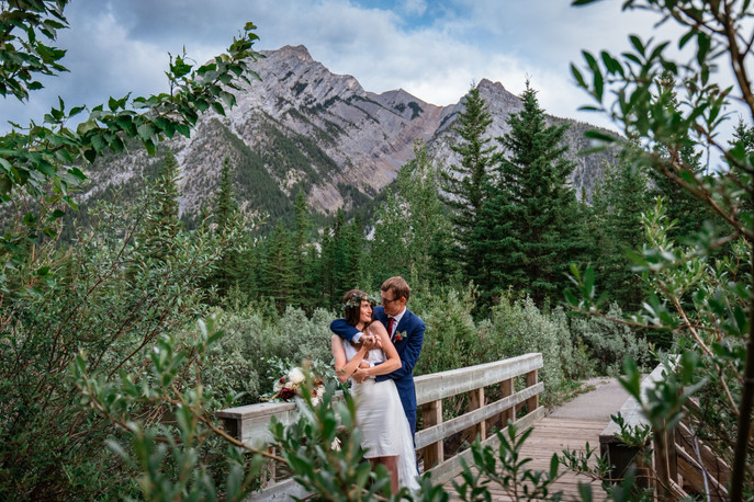 Bride and groom holding one another on a wooden bridge with mountains in the background.