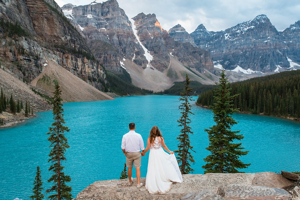 Bride and Groom Stand in front of a lake in between the Rocky Mountains in Alberta