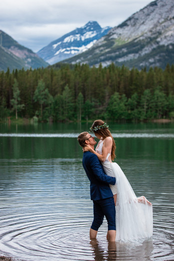 Bride and groom embracing in front of the water. Groom is holding the bride up.