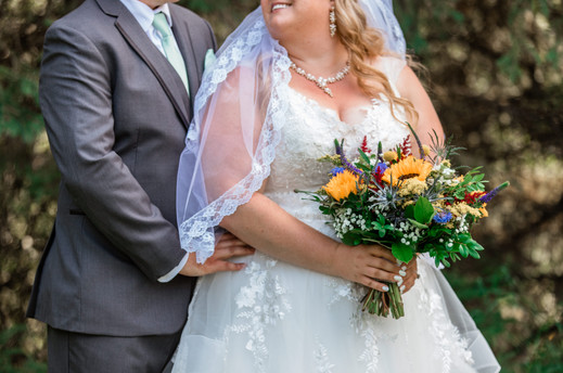 Bride standing in front of her groom and she is looking back and up at him. He is holding her waist. Bride is holding her bouquet.