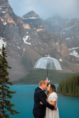 Clear umbrella the couple is holding up with beautiful mountains in the background.