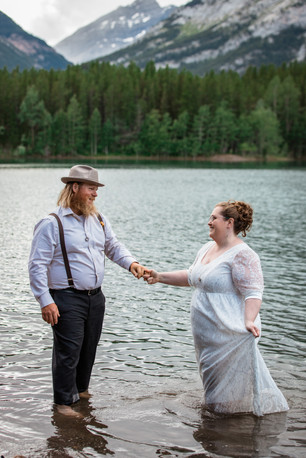 Bride and groom holding hands while standing in the water.